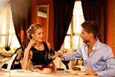 Mladý pár s láhev červeného vína v luxusní restauraci — Stock fotografie