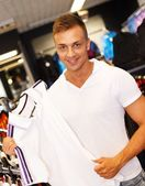 Handsome young man choosing t-shirt in a sport outlet — Stock Photo