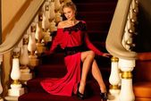 Beautiful young woman in long evening dress sitting on a steps in luxury interior — ストック写真