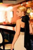Beautiful blond woman in evening dress standing near bar counter — Stock Photo