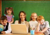 Group of happy classmates with their teacher in class near blackboard — Stock Photo