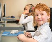 Little redhead schoolboy in front of desktop computer in school — Stock Photo