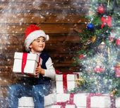 LIttle boy in Santa hat with gift box under christmas tree in wooden house interior — Stockfoto
