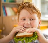 Little redhead schoolboy eating sandwich in class — Stock Photo