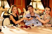 Young friends with glasses of red wine in a luxury restaurant — Foto de Stock