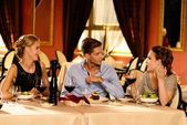 Young friends with glasses of red wine having conversation in a luxury restaurant — Stock Photo