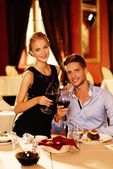 Beautiful young couple with glasses of red wine in luxury restaurant — Foto de Stock