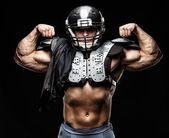 American football player wearing helmet and protective armour — Stock Photo