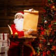 Santa Claus in wooden home interior holding blank wish list scroll — Stock Photo #36566843