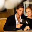 Beautiful young couple with glasses of wine in luxury interior — Стоковая фотография