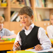 Little schoolboy  sitting behind school desk during lesson in school — Stock Photo
