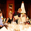Group of young friends with choosing in a luxury restaurant — Stock Photo