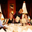 Group of young friends with menus choosing in a luxury restaurant — Stock Photo
