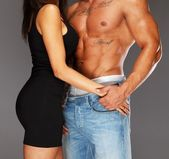 Young woman embracing man with naked muscular torso — Stock Photo