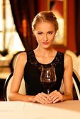 Beautiful young girl with glass of red wine alone in a restaurant — Stock Photo