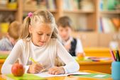 Weinig schoolmeisje zitten achter school bureau tijdens les in school — Stockfoto