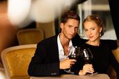 Beautiful young couple with glasses of wine in luxury interior — Stock Photo
