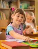 Little schoolgirl sitting behind school desk during lesson in school — Stock Photo