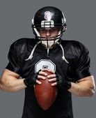 American football player with ball wearing helmet and jersey — Stock Photo
