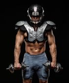 American football player with dumbbells wearing helmet and protective armour — Stock Photo