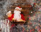 Santa Claus in wooden home interior sitting behind table and writing letters with quill pen — Stock Photo