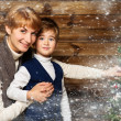 Happy mother and her lIttle boy decorating christmas tree in wooden house interior — Stock Photo #36570927