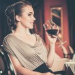 Beautiful young girl with glass of red wine alone in a restaurant — Foto Stock