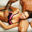 Young beautiful sexy couple in underwear lying on sofa — Stock Photo