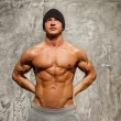 Handsome mwith muscular torso in beanie hat posing — Stock Photo #36571343