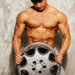 Handsome sporty man with muscular body holding alloy wheel — Stock Photo