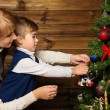 Happy mother and her lIttle boy decorating christmas tree in wooden house interior — Stock Photo #36571541