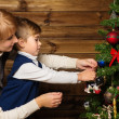 Happy mother and her lIttle boy decorating christmas tree in wooden house interior — Stock Photo