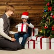 Mother and her lIttle boy in Santa hat opening gift box under christmas tree in wooden house interior — Stock Photo #36571573