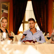 Young friends with glasses of red wine in a luxury restaurant — Stock Photo