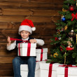 Little boy in Santa hat opening gift box under christmas tree in wooden house interior — Stock Photo