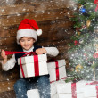 Little boy in Santa hat opening gift box under christmas tree in wooden house interior — Stock Photo #36571747