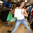 Beautiful happy brunette girl with shopping bag jumping in a sport outlet — Stock Photo