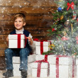 Stock Photo: Little boy with gift box under christmas tree in wooden house interior