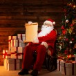Santa Claus in wooden home interior holding blank wish list scroll — Stock Photo
