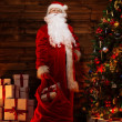 Santa Claus in wooden home interior with sack full of Christmas presents — Stock Photo