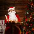 Santa Claus in wooden home interior sitting behind table with milk and oatmeal cookies — Stock Photo