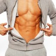Handsome man in grey hoodie showing his abdominal muscles — Stock Photo