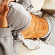 Sporty man in grey hoodie with muscular torso relaxing on sofa — Stock Photo