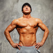 Handsome mwith muscular torso in beanie hat posing — Stock Photo #36576703