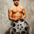 Handsome sporty man with muscular body holding alloy wheel — Stock Photo #36576719