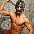 Stock Photo: Gladiator with muscular body with sword and helmet