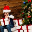 Little boy in Santa hat opening gift box under christmas tree in wooden house interior — Stock Photo #36576763