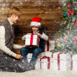Mother and her lIttle boy in Santa hat opening gift box under christmas tree in wooden house interior — Stock Photo