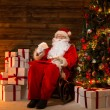 Santa Claus sitting on rocking chair in wooden home interior with letters in hands — Stock Photo