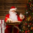 Santa Claus in wooden home interior sitting behind table and writing letters with quill pen — ストック写真
